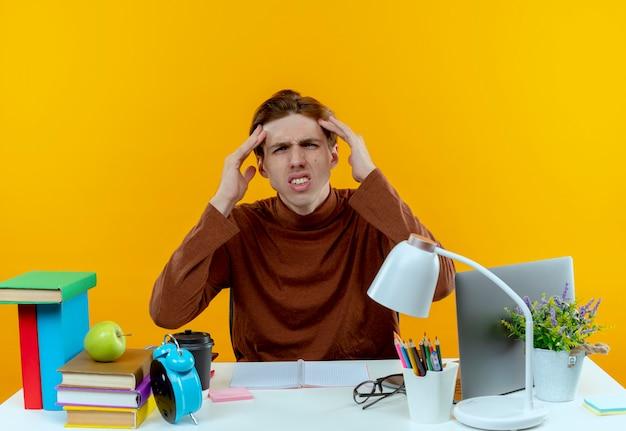Verwirrter junger student, der am schreibtisch mit schulwerkzeugen sitzt, die hände auf die stirn legen