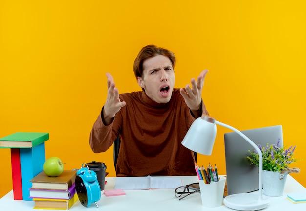 Verwirrter junger student, der am schreibtisch mit schulwerkzeugen sitzt, die hände ausstrecken