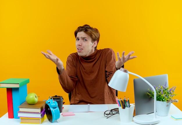 Verwirrter junger student, der mit schulwerkzeugen am schreibtisch sitzt, spreizt die hände