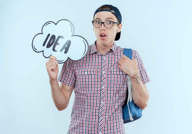 Verwirrter junger student, der rucksack und brille und kappe hält ideenblase trägt