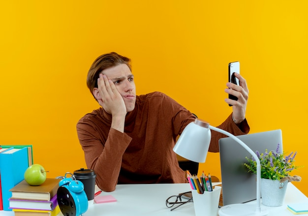 Verwirrter junger studentenjunge, der am schreibtisch sitzt