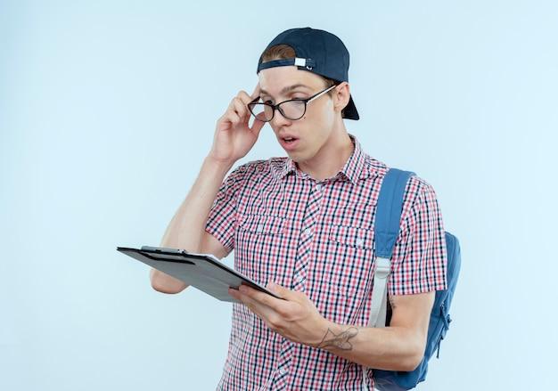 Verwirrter junger studentjunge, der rucksack und brille und mütze trägt, die zwischenablage halten und betrachten