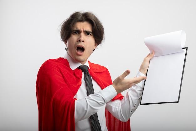 Verwirrter junger superheld, der krawattenhalter trägt und mit der hand auf zwischenablage zeigt