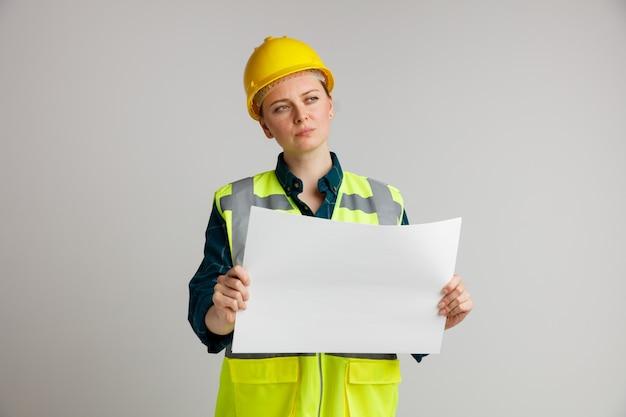 Verwirrter junger weiblicher bauarbeiter, der sicherheitshelm und sicherheitsweste hält, die papier hält, das seite betrachtet