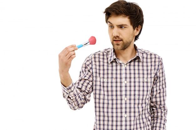 Verwirrter kerl, der auf make-up-pinsel starrt