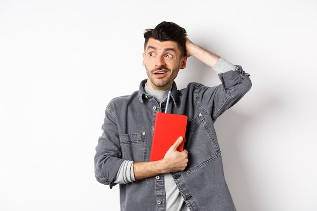 Verwirrter kerl kratzt den kopf und schaut beiseite auf das verwirrte logo, das rotes tagebuch oder planer hält und vor weißem hintergrund steht.