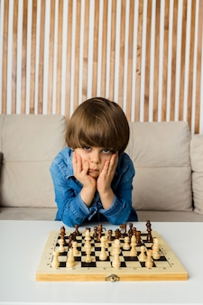 Verwirrter kleiner junge sitzt auf dem sofa und spielt schach im raum