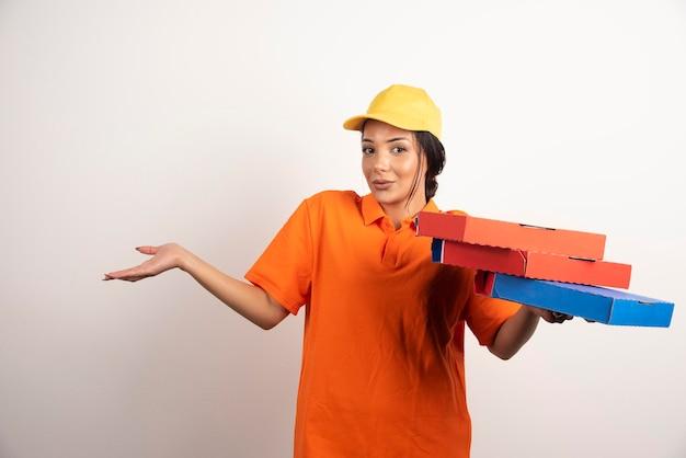 Verwirrter kurier in uniform, der einen haufen pizzen hält.