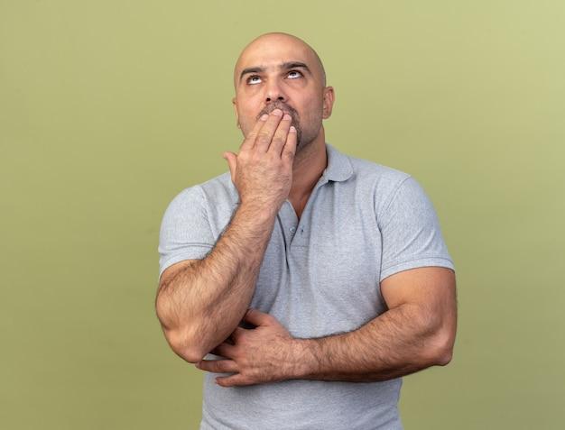 Verwirrter, lässiger mann mittleren alters, der die hand auf dem mund hält, der isoliert auf einer olivgrünen wand nach oben schaut