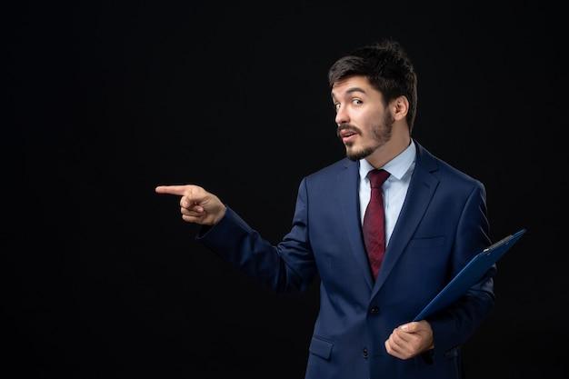 Verwirrter männlicher büroangestellter im anzug, der dokumente hält und etwas auf der rechten seite auf isolierte dunkle wand zeigt