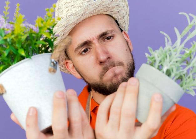 Verwirrter männlicher gärtner, der gartenhut trägt, betrachtet blumen in blumentöpfen