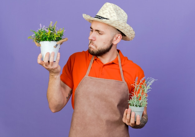 Verwirrter männlicher gärtner, der gartenhut trägt, hält blumentöpfe