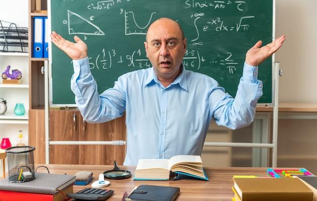 Verwirrter männlicher lehrer mittleren alters sitzt am tisch mit schulwerkzeugen, die die hände im klassenzimmer ausbreiten