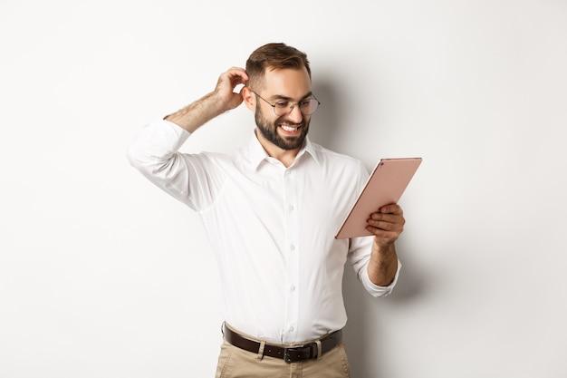Verwirrter männlicher manager, der verwirrt auf digitales tablett schaut, kopf zweifelhaft kratzt, stehend