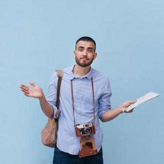 Verwirrter männlicher reisender, der seine schulter hält die karte steht gegen blaue wand zuckt