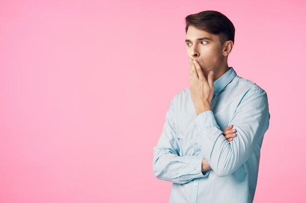Verwirrter mann auf einem rosa hintergrund im studio