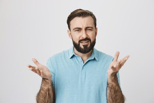 Verwirrter mann blinzelte und breitete die hände seitlich befragt aus