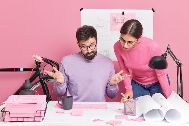 Verwirrter mann breitet hände aus und sieht verwirrend auf papiere, die seine kollegin in der nähe von arbeiten an der blaupause eines neuen projekts posiert, diskutieren ideen zur illustration. brainstroming-meeting für engineering.