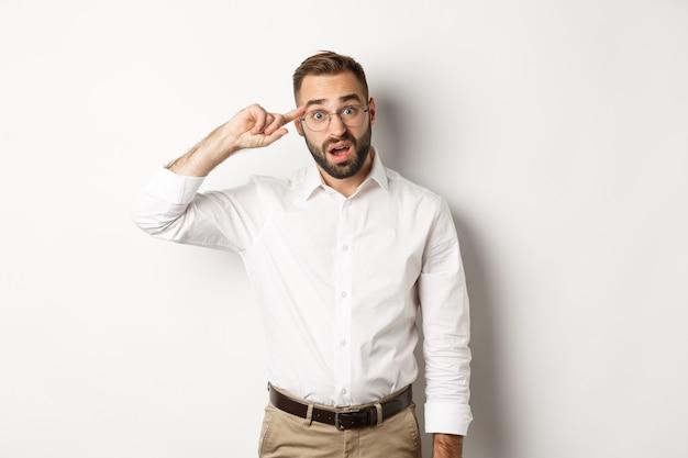 Verwirrter mann, der auf den kopf zeigt, angestellten schimpft, auf etwas seltsames reagiert und weiß steht