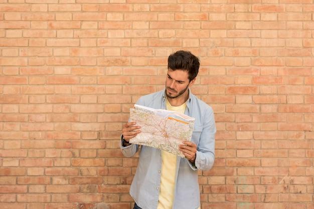 Verwirrter mann, der karte betrachtet