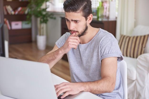 Verwirrter mann, der vor seinem computer sitzt