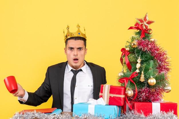 Verwirrter mann der vorderansicht mit krone, die tasse nahe weihnachtsbaum und geschenke hält