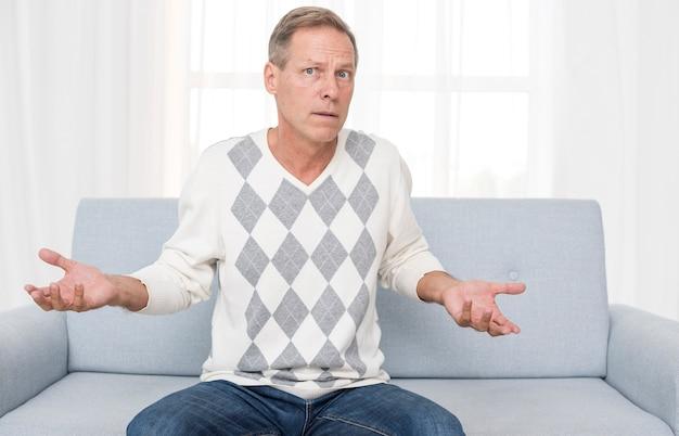 Verwirrter mann des mittleren schusses, der auf der couch sitzt