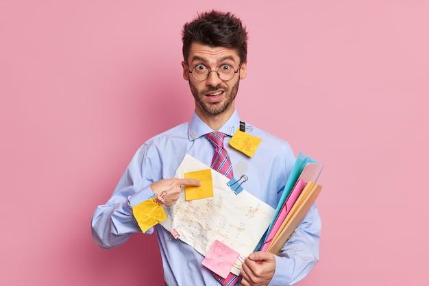 Verwirrter mann manager zeigt auf sich selbst und fragt, wer mich für kurze zeit auf die projektarbeit vorbereiten soll. er trägt formelle kleidungsposen