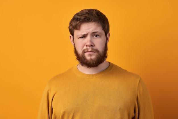 Verwirrter mann mit dickem ingwerbart, zieht die augenbrauen hoch, reagiert auf falsche nachrichten von freunden, schaut direkt in die kamera