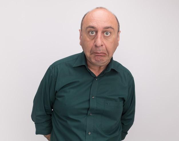 Verwirrter mann mittleren alters, der grünes t-shirt trägt, lokalisiert auf weißer wand