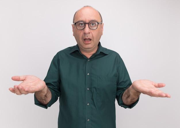 Verwirrter mann mittleren alters, der grünes t-shirt und gläser trägt, die hände lokalisiert auf weißer wand verbreiten