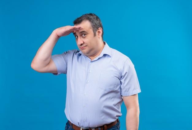 Verwirrter mann mittleren alters im blau gestreiften hemdmann, der weit weg schaut und hand auf der stirn auf einem blauen raum hält