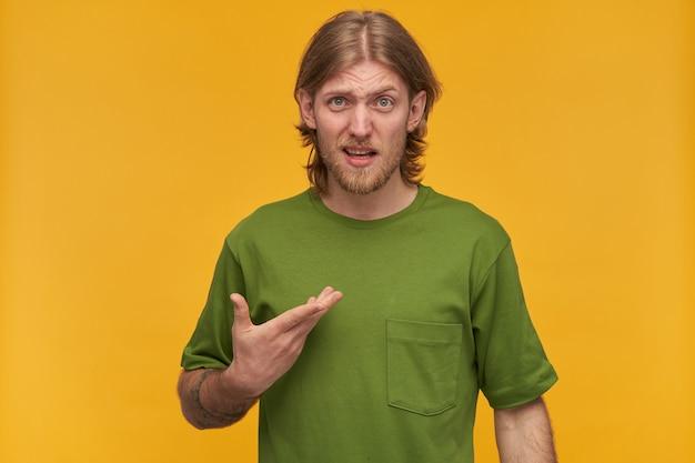 Verwirrter mann, unglücklicher kerl mit blonden haaren, bart und schnurrbart. grünes t-shirt tragen. hat tätowierung. er zeigte verwirrt auf sich. isoliert über gelbe wand