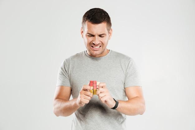Verwirrter mann versucht rubiks würfel zu lösen.