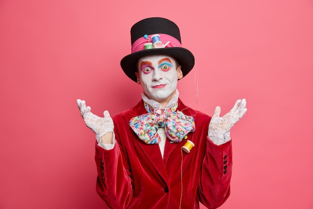Verwirrter mann zögert, ob eine verrückte teeparty die hände in ahnungsloser geste hebt, kommt auf festival trägt kostüm und hut posiert gegen rosa wand