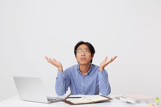 Verwirrter nachdenklicher asiatischer junger geschäftsmann in gläsern, der mit laptop und notizbuch am schreibtisch sitzt und copyspace auf beiden handflächen über weißer wand hält
