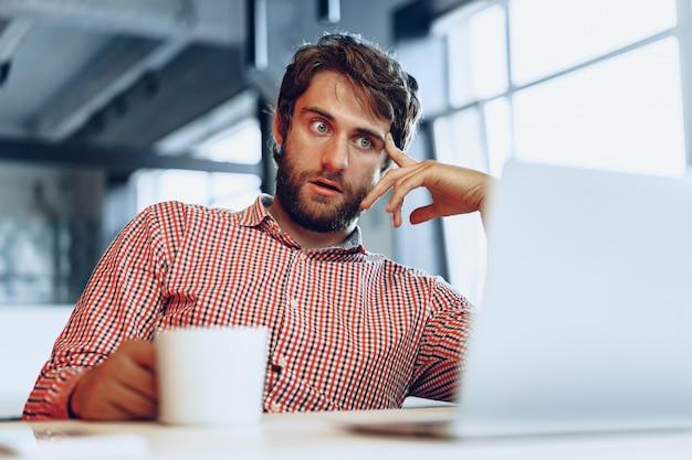 Verwirrter nachdenklicher geschäftsmann, der an seinem arbeitstisch in einem büro sitzt. geschäftskonzept