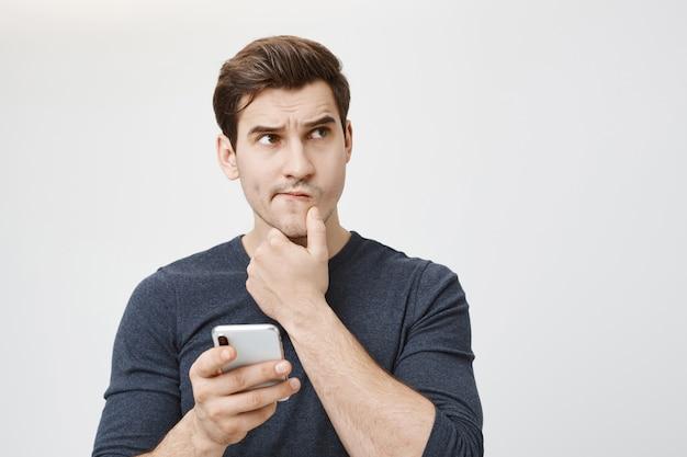 Verwirrter nachdenklicher mann, der denkt, während er smartphone hält