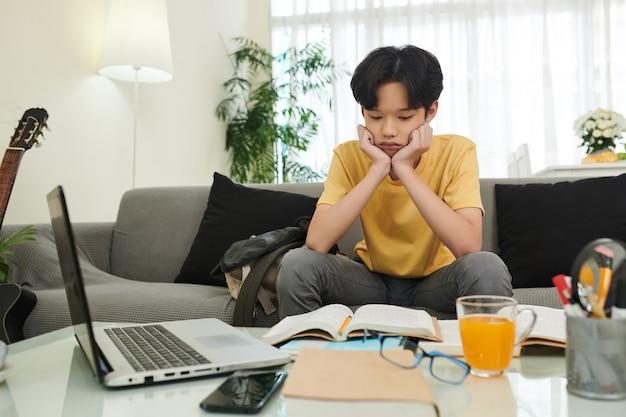 Verwirrter oder gelangweilter teenager, der geöffnetes studentenbuch mit schwierigem artikel betrachtet