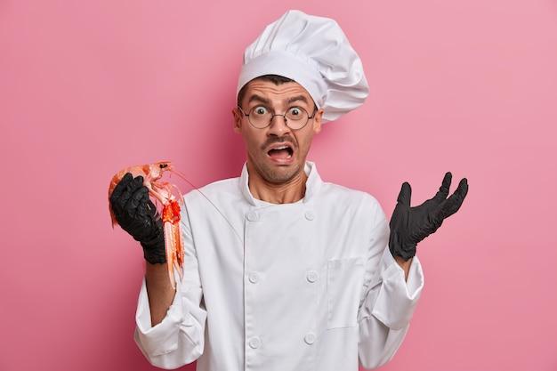 Verwirrter professioneller überraschter koch hält meeresfrüchteprodukt, bereitet köstliches gourmetgericht zu, ruft negativ aus
