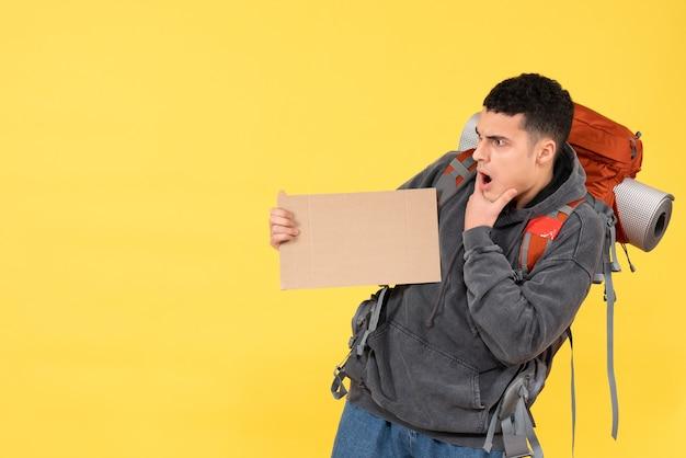 Verwirrter reisender der vorderansicht mit rotem rucksack, der pappe hält