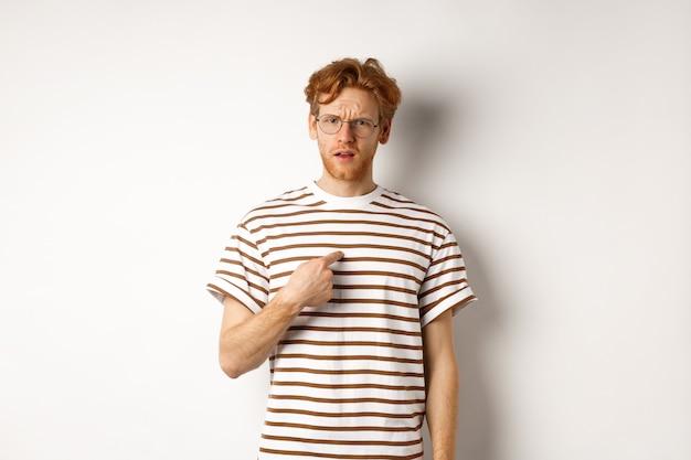 Verwirrter rothaariger mit brille, der auf sich selbst zeigt und in die kamera schaut, weißer hintergrund.