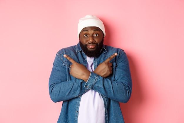 Verwirrter schwarzer mann bittet um hilfe bei der auswahl, zeigt zur seite und starrt in die kamera, trifft eine entscheidung und steht über rosa hintergrund