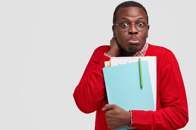 Verwirrter schwarzer mann sieht verwirrt aus, trägt papiere mit stift, gekleidet in roten pullover