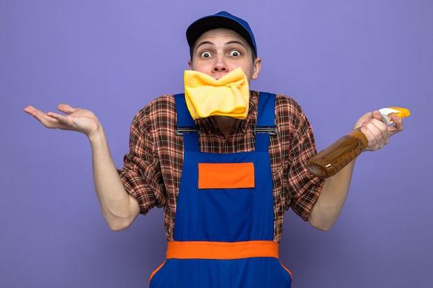 Verwirrter, sich ausbreitender junger reinigungsmann mit uniform und mütze, der einen lappen in den mund steckt, der reinigungsmittel hält