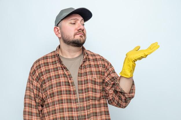 Verwirrter slawischer putzmann mit gummihandschuhen, der seine hand anschaut