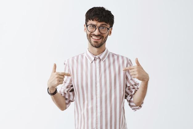 Verwirrter stilvoller bärtiger kerl, der mit brille gegen die weiße wand aufwirft
