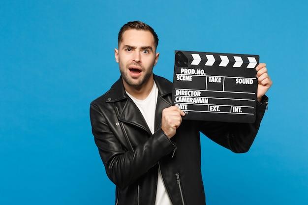 Verwirrter, stylischer junger unrasierter mann in schwarzer jacke, weißem t-shirt, der in der hand hält, film macht filmklappe einzeln auf blauem hintergrund studioporträt. menschen lifestyle-konzept. kopieren sie platz.