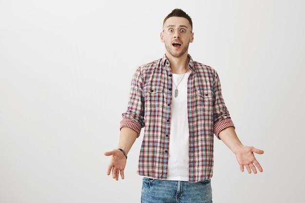 Verwirrter und ahnungsloser junger mann posiert