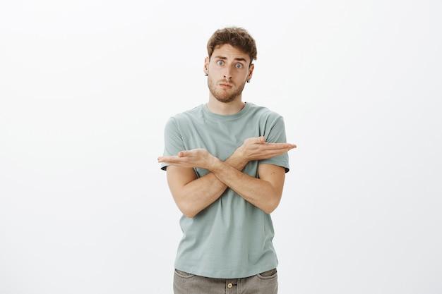 Verwirrter und besorgter gutaussehender männlicher mitarbeiter im trendigen t-shirt, der die hände über der brust kreuzt und nach links und rechts zeigt und gefragt wird, welche richtung er wählt